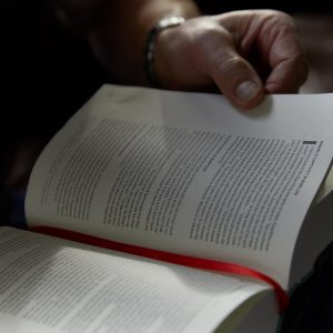 Man turning pages in a Bible